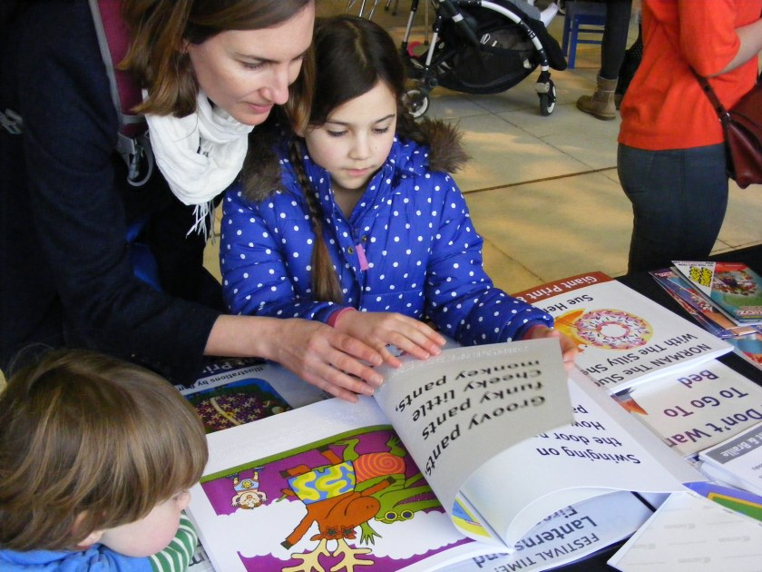 Picture of a young mother in a black coat and dark hair listens to her daughter in a blue coat reading an accessible version of Pant at the Imagine Festival at the Southbank. Her son is also engrossed in the big, colourful pictures in the book. The mother and daughter are both running their fingers over the Braille at the bottom of the page.