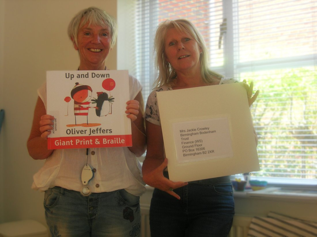 Image of Eileen Finch and Chrissy standing side by side and holding up a copy of Up and Down written and illustrated by Oliver Jeffers, and a funding application Chrissy is about to send out.