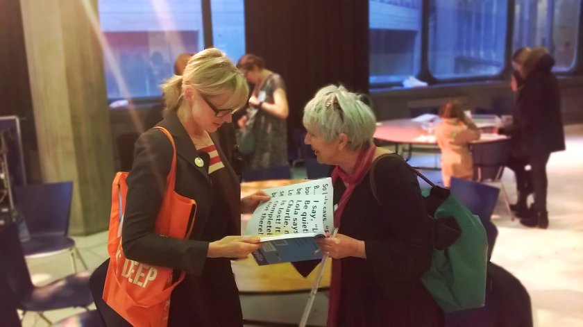 Picture of Eileen Finch and Lauren Child chatting and holding an accessible version of Charlie and Lola between them.