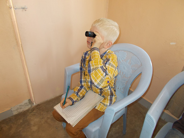 Image of a small blonde boy sitting in a white plastic chair, holding a telescopic magnifier to his left eye while taking down notes on a notepad on his knees using the pen in his right hand. He is wearing a yellow and blue checked shirt and light brown - chocolate like trousers.